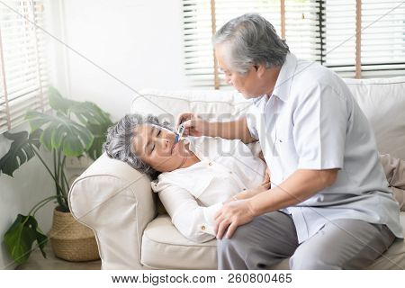 Sick Old Woman With Thermometer Laying In Sofa And Husband Hand Taking Temperature. Husband Checking