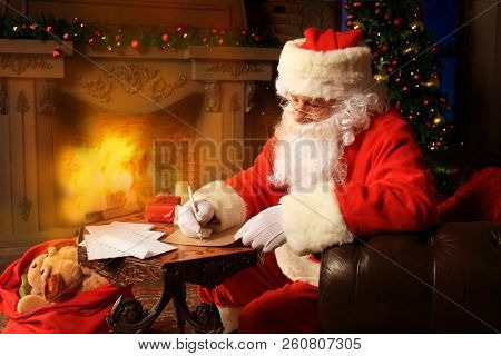 Portrait Of Happy Santa Claus Sitting At His Room At Home Near Christmas Tree And Answering Christma