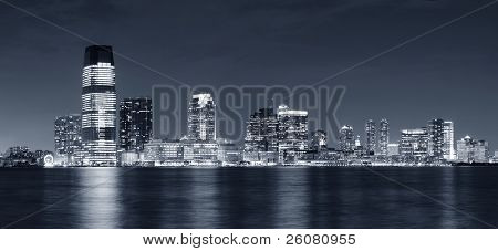 Jersey City skyline with skyscrapers at night black and white over Hudson River viewed from New York City Manhattan downtown.