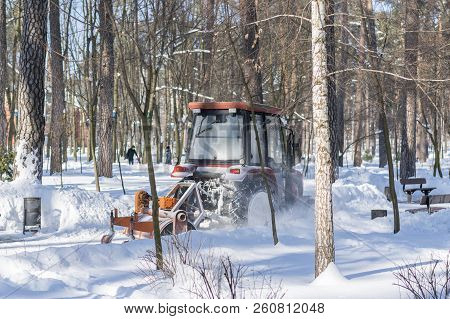 A Small Tractor With A Rotating Brush Clears A Wide Road In The City Park From The Fresh Fallen Snow