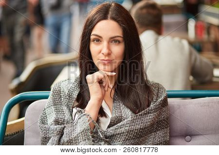 Portrait Of Beautiful Self Confident Young Female Holds Hand Under Chin, Looks Directly At Camera, W