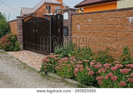 Brown Metal Gate And Brick Fence Near Decorative Green Plants And Flowers