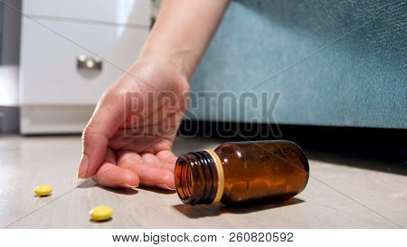 Closeup image of female hand and pills lying on floor at bedroom. Drug addiction. Overdose of narcotics or medications. Death of patient poster