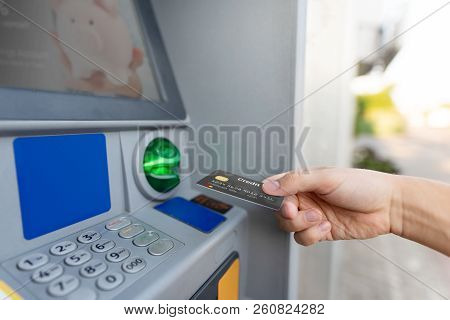 Man Hand Puts Credit Card Into Atm. Money Is Withdrawn From An Atm.