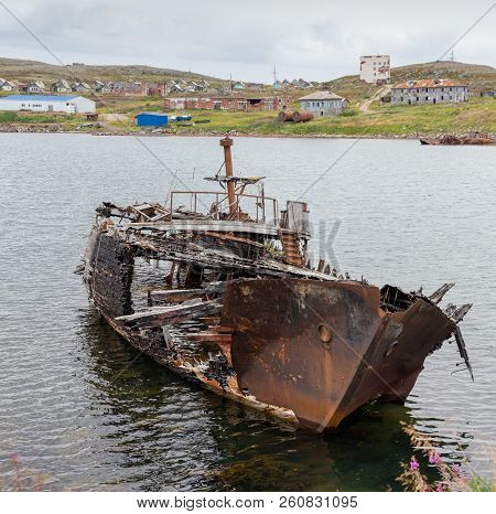 Rotting, Abandoned Ship On A Water Of Sea Bay Against The Background Of An Abandoned Village, Symbol