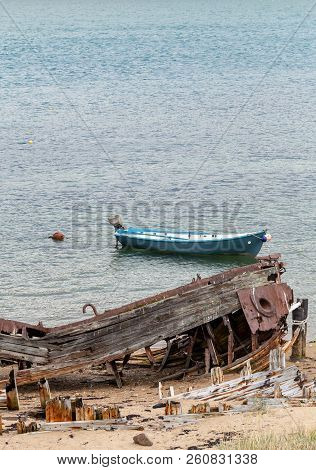 Remains Of A Destroyed Abandoned Ship On The Shore, A Symbol Of Decadence And Degradation, And Moder