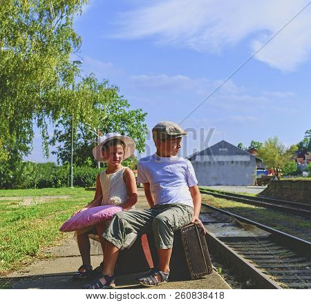 Adorable Little Children On A Railway Station, Waiting For The Train With Vintage Suitcases. Traveli