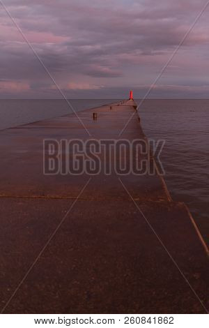 A Lighthouse Pier On Lake Michigan At Dusk With Pink Clouds Reflected In The Water.  Sheboygan, Wisc