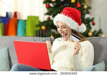 Excited Girl Holding A Card Shopping Online On Christmas Sitting On A Couch In The Living Room At Ho