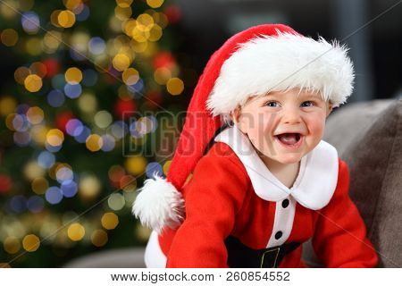 Baby Laughing Wearing Santa Claus Disguise On A Couch At Home In Christmas With A Tree In The Backgr