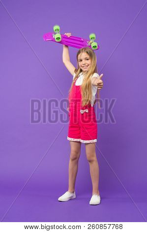 Kid Girl Relax Hold Penny Board. Active Leisure Concept. Girl Raise Up Penny Board And Show Thumbs U