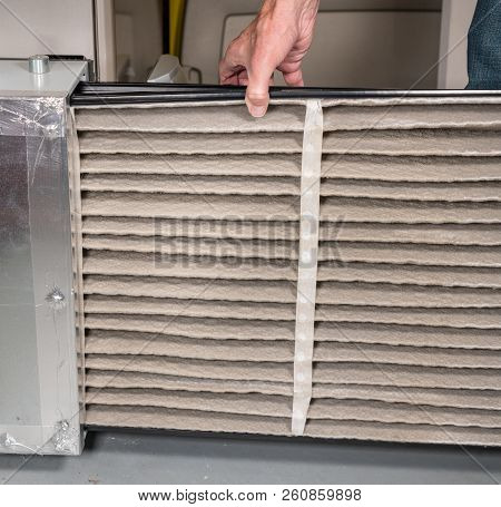 Senior Caucasian Man Changing A Folded Dirty Air Filter In The Hvac Furnace System In Basement Of Ho
