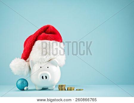 Piggy Bank Wearing Santa Hat - Saving For Christmas Concept