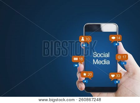 Hand Holding Mobile Smart Phone, With Notification Icons. Social Media On Mobile Phone
