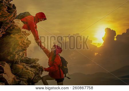 Male And Female Hikers Climbing Up Mountain Cliff And One Of Them Giving Helping Hand. People Helpin