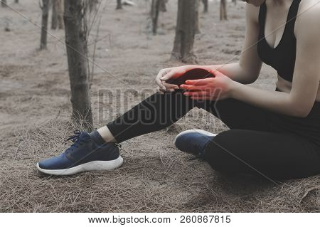 Unhappy Young Woman Sitting In The Garden, Grabbing An Ankle, Unable To Start Running Because Of Spo