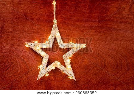 Rustic Christmas Star Decoration Wrapped In Lights On A Beautiful Red Stained Wood Background