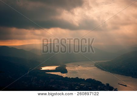 Rays Of Sun Shining Through The Clouds. The River Runs Into The Distance. The River Is Calm. The Sky