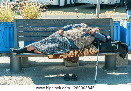 Homeless Barefooted Woman Sleep On The Wooden Bench On Urban Street In The City On The Sidewalk