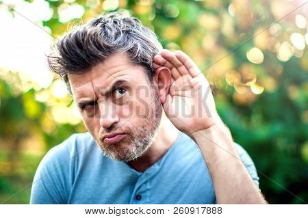 Listening.close Up On Hand And Ear Listening For A Quiet Sound Or Paying Attention Outdoor