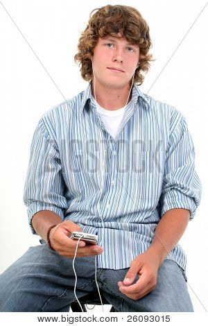 Attractive Sixteen Year Old Teen Boy listening to headphones in casual over white background.  Light brown curly hair and hazel eyes.
