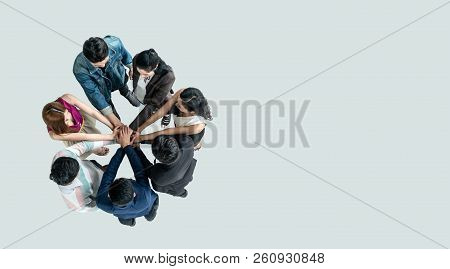 Top View Of People In Team Stack Hands Together As Unity And Teamwork In Office. Young Asian Team An