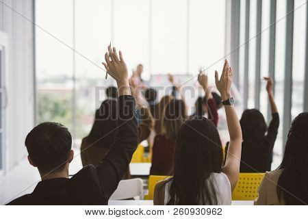 Raised Up Hands And Arms Of Large Group In Seminar Class Room At Conference