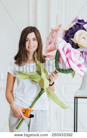Vertical Shot Of Professional Young Female Designer Or Florist Holds Big Bouquet, Uses Garden Pincep