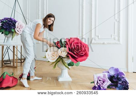 Busy Woman Dressed Casually, Decorates Hall With Flowers For Festive Event. Female Florist Prepares