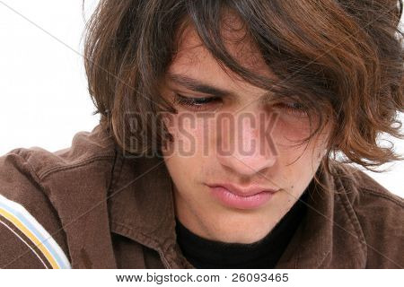 Close up of teen boy crying. Tears in eyes and on cheeks.