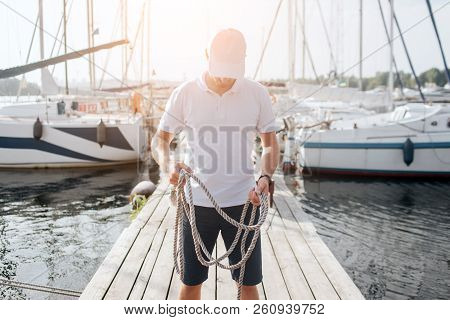 Picture Of Serious And Concentrated Young Man. He Stands On Pier And Look Down. Guy Holds Ropes In H