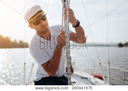 Young Sailor In Sunglasses And Cap Holds And Moves Ropes With Both Hands. He Is Calm And Concentrate