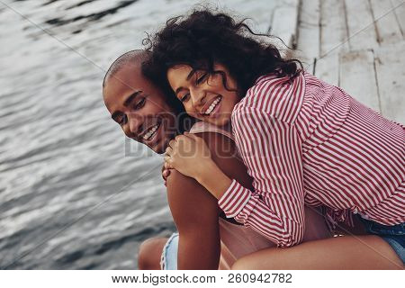 Romantic Couple. Beautiful Young Couple Embracing And Smiling While Sitting On The Pier