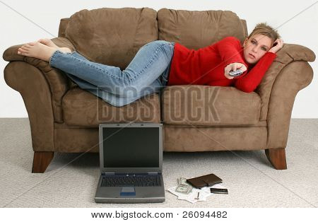 Beautiful young woman taking a break from balancing her bills online.  Laptop, cash, credit card, bills and checkbook on the floor in front of her as she relaxes on the couch watching tv.