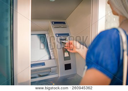 Young Woman Inserting Credit Card Into Atm Machine To Checkout Account Balance And Withdraw Money Fr