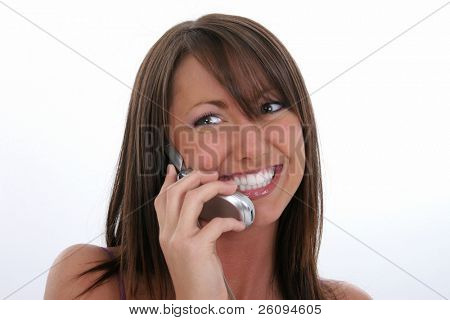 Happy young woman speaking on cellphone.  Beautiful smile and great teeth.  Lovely tan complextion and brown hair.