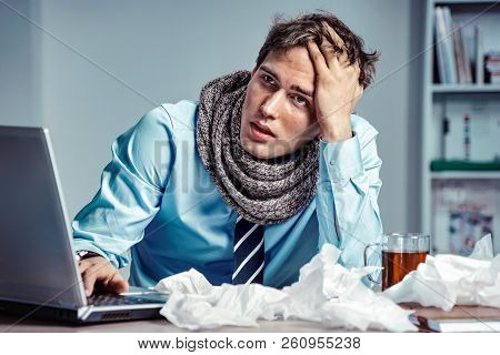 Bad Feeling. Sick Worker Has High Temperature. Photo Of Young Man In Office Suffering Virus Of Flu.