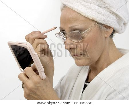 Vrouw in de jaren vijftig appying make-up.  Het dragen van witte robe en handdoek in haar. In de studio opgenomen.
