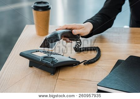 cropped image of businesswoman taking handset of stationary telephone in office poster