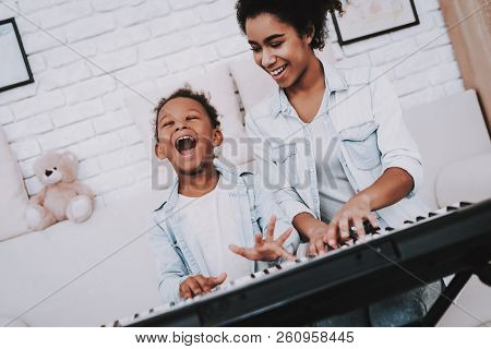 Child With Mother Play On Piano. Childhood With Mother. Hobbies With Mother. Smile Mother With Young