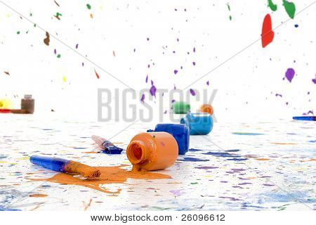 Bottles of washable kids paint and brushes split on the floor.