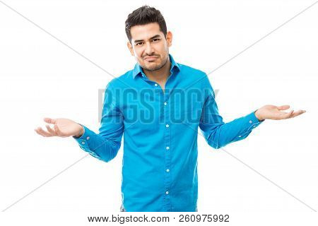 Portrait Of Unsure Man Wearing Blue Shirt While Shrugging His Shoulders Over White Background