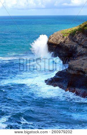 Large Wave Crashes Against A Cliff At Kilauea Point On The Island Of Kauai, Hawaii.  Horizon Is Turq