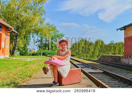 Cute Happy Girl Holding Plush Toy On A Railway Station, Waiting For The Train With Vintage Suitcase.