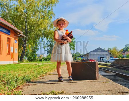 Cute Girl Holding Stuffed Animal On A Railway Station, Waiting For The Train With Vintage Suitcase.