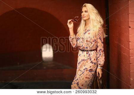 Beautiful Blond Tourist Woman With Sun Glasses In Floral Print Dress On Red Square Brick Wall Backgr