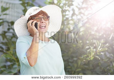 Aged Woman Talking On Phone. Old Lady In The Park. Sunny Day, Happy Mood. Happysenior Woman With Pho