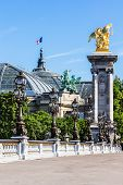 Ornate renaissance street lamps and gilded sculpture on the Pont Alexandre III Bridge with Grand Palais (Grand Palace) in the summer morning. Paris, France poster
