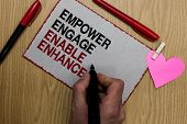 Text sign showing Empower Engage Enable Enhance. Conceptual photo Empowerment Leadership Motivation Engagement Written sticky note clip pinch heart hand hold marker red pen on wooden desk. poster