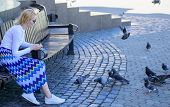Woman tourist or citizen toss crumbs for pigeons. Group doves on city square waiting treats. Girl feeding dove birds urban background. Girl blonde woman relaxing city square and feeding pigeons poster